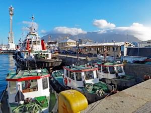 Südafrika | Kapstadt, Hafen in der V&A Waterfront mit dem Tafelberg im Hintergrund und einigen Fischerbooten im Vordergrund bei blauem Himmel