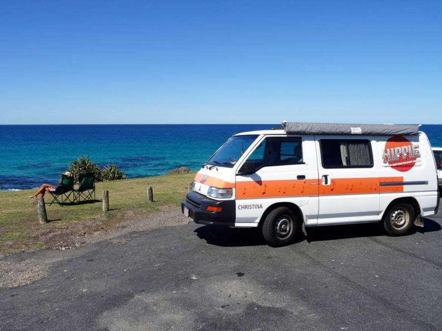 Australien | Camping, flexibel an den schönsten Orten. Nahaufnahme unseres Hippie Campers mit dem Ozean und Karin im Campingstuhl die das Panorama genießt