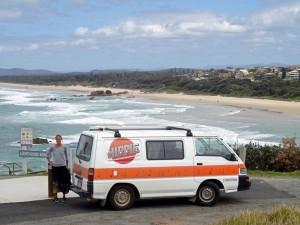Australien | Camping in der Nähe von Byron Bay am Leuchtturm in New South Wales. Karin steht vor unserem Hippie Camper mit Panoramablick auf die Bucht direkt am Meer