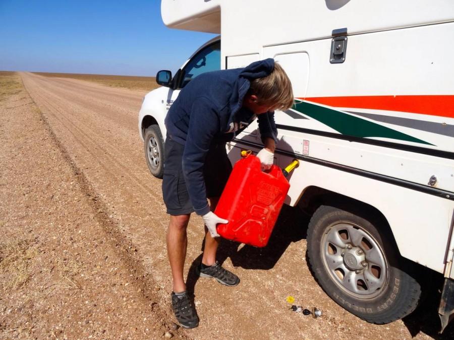 Australien | Camping im Outback, ein Benzin-Reserve-Kanister schadet nie. Henning füllt unseren Camper mit Benzin aus einem roten Kanister inmitten der Offroad-Straße auf dem Odanatta Track