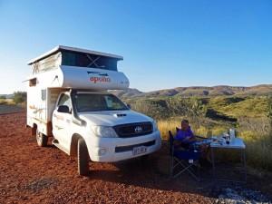 Australien | Camping im Outback. Hier im Northern Territory in der Nähe des Kings Canyon. Henning und unser Cheapa 4 WD Camper in Nahaufnahme vor dem Panorama der umliegenden Gebirgsketten