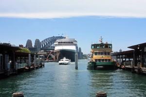 Australien | Sydney, Fähranleger Circular Quay. Blick von Land auf eine Fähre im Hafen mit der HArbour Bridge im Hintergund und einem Kreuzfahrtschiff
