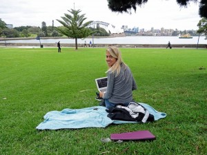 Australien | Sydney, Picknick im Botanischen Garten mit Blick auf die Oper und Harbour Bridge. Karin sitzt auf einer Decke im Gras mit dem Laptop in der Hand