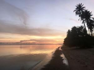 Thailand |Koh Phangan, Sonnenuntergang am Strand Ao Bang Charu. Rötlich gefärbter Himmel spiegelt sich im Meer an von Palmen gesäumten Strand