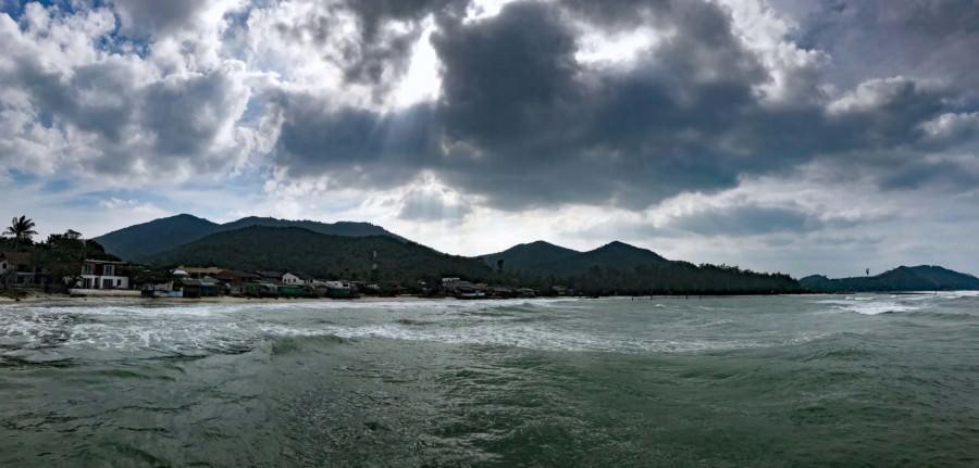 Thailand |Koh Phangan, Panorama der Bucht und Strand Ao Chaloklum, mit vielen Fisch-Restaurants. Wolkenverhangener Himmel, Meer, kleine bunte Hütten vor dem bergigen Inland der Insel