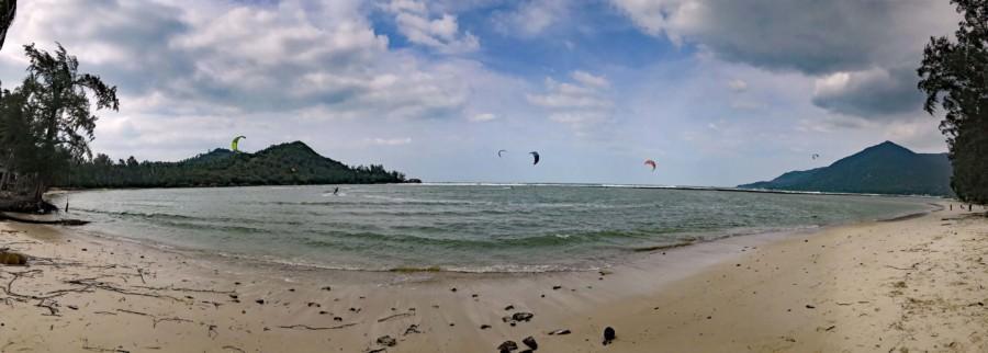 Thailand |Koh Phangan, Kitsurfer am Strand Ao Chaloklum Strand. Blick auf Strand, Meer, Wellen und ein die Segel der Surfer