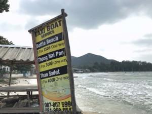 Thailand, Koh Phangan, Preise fuer Taxi-Boote am Strand Ao Chaloklum zum Bottle Beach, Thong Nai Pan und Than Sadet. Schild in gelb und schwarz vor dem Meer