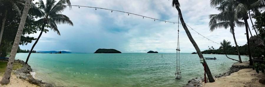 Thailand |Koh Phangan, Strand der Bucht Ao Nai Wok zur Regenzeit im November. Türkis-blaues Wasser, Palmen und bewölkter Himmel über der Insel
