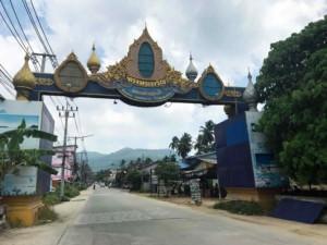 Thailand | Koh Phangan, Hauptstraße durch den Ort Baantai. Tor als Eingang zum Ort über der Straße
