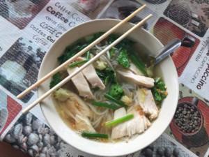 Thailand |Koh Phangan, der Klassiker Chicken Rice Noodle Soup. Schalte mit Stäbchen, Hühnchen, Reisnudeln, Gemüse, klare Suppe und Gewürze auf einem Tisch