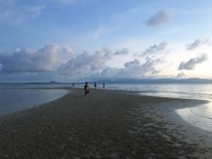 Thailand |Koh Phangan, Sonnenuntergang bei Ebbe am Strand Haad Baan Tai. Blick auf das Meer mit einigen Schäfchen-Wolken und rötlich gefärbtem Himmel, den Strand und einige Menschen