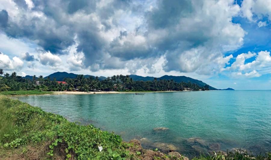 Thailand |Koh Phangan, Panorama auf den Strand Haad Bantai. Blick auf die Bucht mit Palmen, blauem Wasser bei Sonne mit Wolken