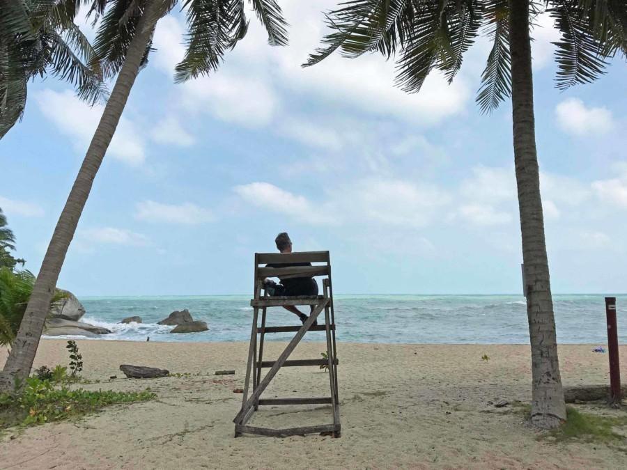 Thailand | Koh Phangan, Ausblick in der Bucht am Strand Haad Than Sadet. Henning auf einem Stuhl von hinten mit Blick auf das Meer, den Horizont und feinen Sand gesäumt von Palmen