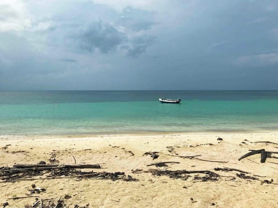 Thailand |Koh Phangan, Traumhafte Kulisse am Strand Haad Yao West. Ein einsames Boot in türkisfarbenem Wasser, gelber feiner Sand, dunkle Wolken über dem Meer
