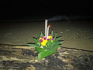 Thailand |Lichterfest in Koh Phangan, ein buntes Blumengesteck mit brennender Kerze