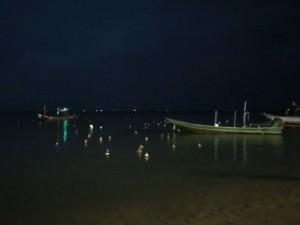 Thailand |Lichterfest in Koh Phangan am Thongsala Pier. Schwimmende Blumengestecke mit Kerzen im Meer bei Dunkelheit