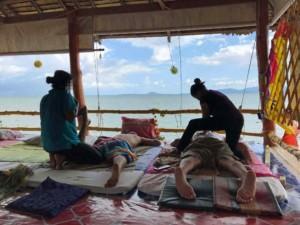 Thailand |Koh Phangan, Massage am Baan Tai Strand. Zwei Männer liegen auf Matratzen und 2 Masseurinnen massieren mit Blick auf blaues Meer