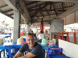 Thailand | Koh Phangan, Phantip Market, Essen bei typisch thailändischen Garküchen. Henning wartet auf seine Chicken Noodle Soup