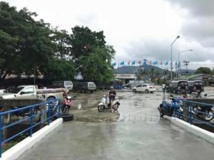 Thailand |Koh Phangan, Ankunft am Pier in Thongsala. Blick auf die Straße Richtung Stadt, wartende Mopeds und Songtheaws