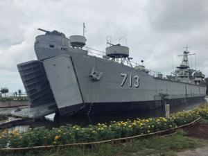 Thailand | Sehenswürdigkeiten, das Phangan Royal Navy Ship in Thongsala. Kriegsschiff mit Aufschrift 713 in grau, gelbe Blumen im Vordergrund