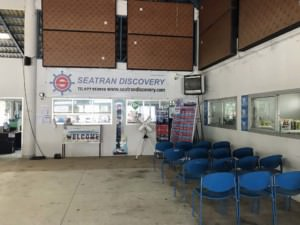 Thailand | Koh Phangan Schalter für Fähren und Tickets von Seatran Discovery in Thongsala. Blick auf die Verkaufsstelle mit blauen Stühlen zum Warten