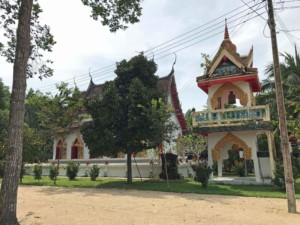 Thailand | Koh Phangan, Wat Pho Tempel. Blick auf die bunte Tempelanlage umgeben von Bäumen