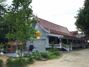 Thailand |Koh Phangan, Wat Phu Khao Noi Tempelanlage. ein weißer Buddha bewacht das Haupthaus des Tempels