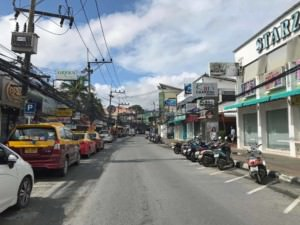Thailand| Koh Samui, die Hauptstraße durch Chaweng, einer der beliebtesten Orte der Insel. Blick auf die Straße mit zahlreichen Shops, Autos und Roller