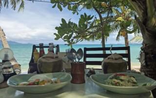 Thailand |Koh Samui, Mittagessen direkt am Strand mit traumhaftem Ausblick, hier am Maenam Beach. Zwei Teller mit Reis und Curry, zwei Kokosnüsse auf gedecktem Tisch, im Hintergrund das türkisfarbene Meer