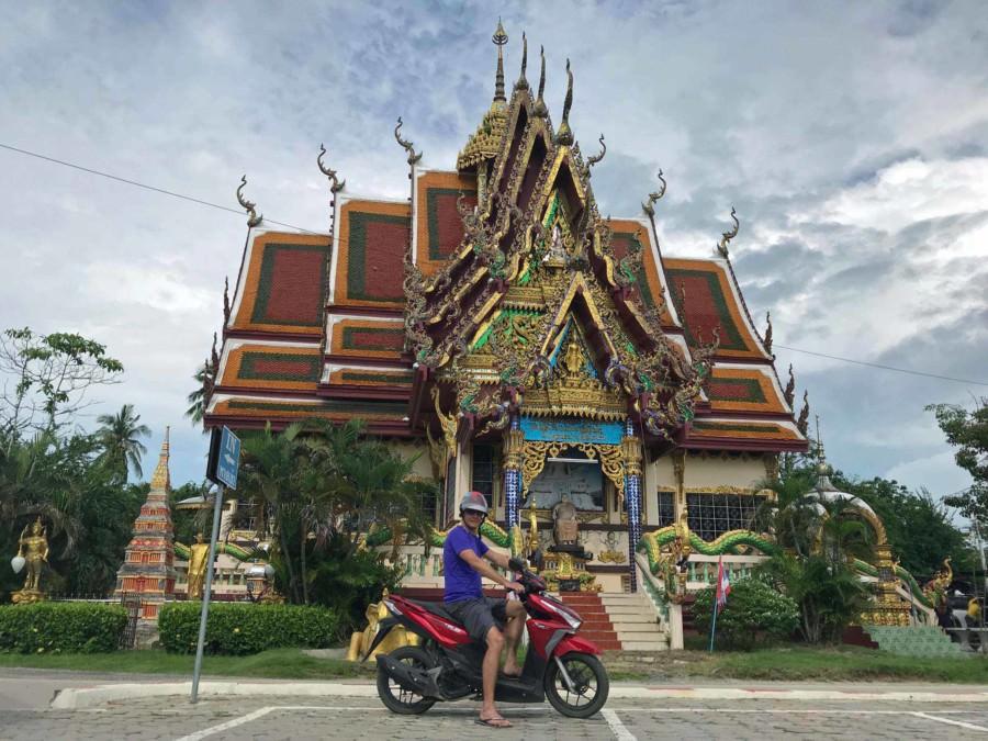 Thailand | Koh Samui, die Tempelanlage Wat Plai Laem ist so groß, dass man mit dem Roller durchfahren kann. Henning auf dem Moped vor einem bunten Tempel