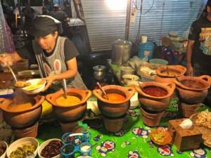 Thailand |Verschiedene Currys auf dem Nachtmarkt in Krabi. Eine Frau vor einigen Tontöpfe mit Curry-Varianten bei Auffüllen einer Schale