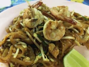 Thailand |Essen auf dem Nachtmarkt am Pier in Krabi: der Klassiker Phad Thai. Reisnudeln mit Garnelen und Gemüse auf einem rosa Teller