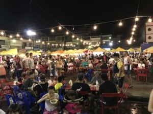 Thailand |Nachtmarkt in Krabi ein Muss: hier ein großer Platz auf dem Nachtmarkt in der Walking Street. Tische mit Stühlen besetzt von Nachtmarkt-Besuchern beim Essen