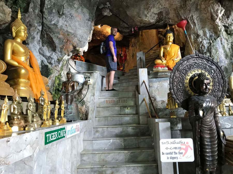 Thailand |Top-Sehenswürdigkeit in Krabi: Aufgang zur Tiger Cave innerhalb der Tempelanlage. Blick auf die Stufen gesäumt von Buddha-Statuen und Henning