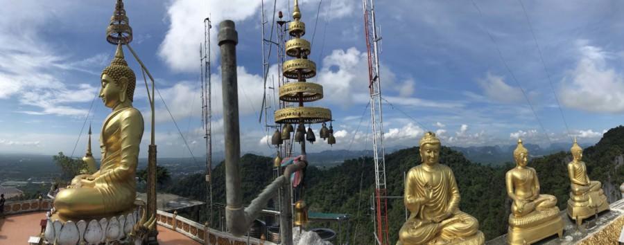 Thailand |Panorama auf dem Berg des Tiger Cave Tempels oder Wat Tham Sua. Goldene Buddha-Statuen vor Kreidefelsen bedeckt von Urwald bei blauem Himmel