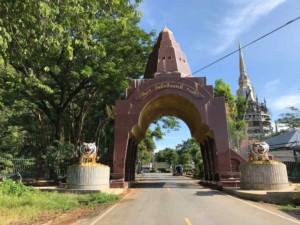 Thailand |Eingang zum Tiger Cave Tempel bei der Tagestour von Krabi. Blick auf ein Tor bewacht von zwei Tiger-Statuen am Straßenrand