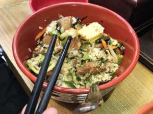"""Einer unserer Tipps ist Südkoreanisches Essen: """"Bibimbap"""" ist Reis mit verschiedenen Gemüsen und Schwein oder Tofu. Schale mit Essen und Stäbchen"""