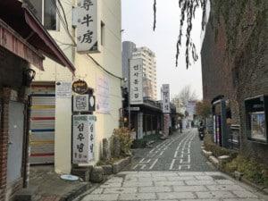 Straße im Bukchon Hanok Dorf. Blick auf einige mit Schriftzeichen beschriebenen Schilder an den Hauseingängen