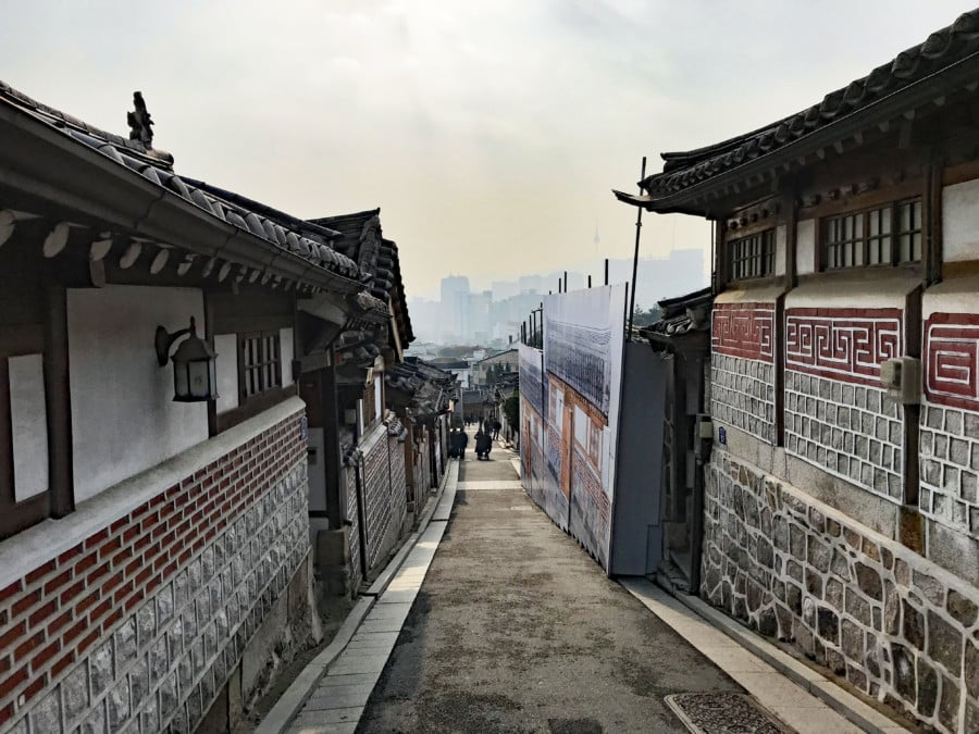 Südkorea | Stadtteil & einer unserer Tipps in Seoul: Bukchon Hanok Village. Blick in eine traditionelle Straße mit der modernen Stadt am Horizont