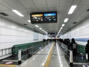 Südkorea | Weg zum AREX-Express-Zug am Flughafen Seoul Incheon. Blick auf die Rolltreppen im Untergrund mit vielen Menschen auf dem Weg zur Bahn
