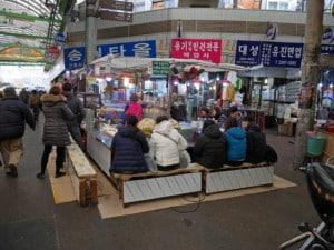 Südkorea | Seoul, im Gwangjang Market gibt es Bänke beheizt. Blick auf einen Esstand in der Markthalle