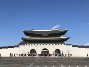 Südkorea | Seoul, Blick vom Gwanghwamun Plaza auf den Gyeongbokgung Palast bei blauem Himmel, Menschen warten auf den Einlass
