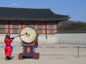 Trommelschlag zur Wachablösung im Gyeongbokgung Palast. Blick auf eine große Trommel und einen bunt gekleideten Mann, der die Trommel schlägt