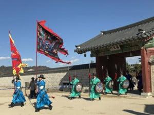Sehenswürdigkeiten & interessante Orte: Wachablösung im Gyeongbokgung Palast. Bunt gekleidete Männer mit Fahnen, Schild und Lanze marschieren in den Innenhof des Palast