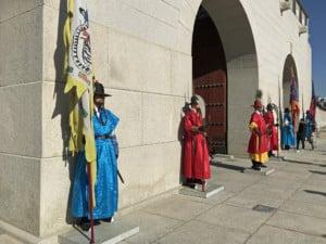 Interessante Orte | Wachen vor dem Gwanghwamun-Gate, dem Eingang zum Gyeongbokgung Palast. Bunt gekleidete Männer mit Helm, Fahne, Lanze und Schild stehen stramm vor den Eingangstoren