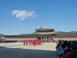 Interessante Orte | typischer Wachwechsel im Gyeongbokgung Palast und seine Zuschauer. Menschen hinter Absperrungen beobachten die marschierende Mann in roten Kleidern bei blauem Himmel