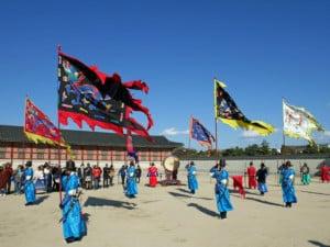 Südkorea | Seoul, Gyeongbokgung Palast: die Fahnen werden beim Wachwechsel geschwungen, bunt gekleidete Männer bei blauem Himmel im Innenhof des Palastes