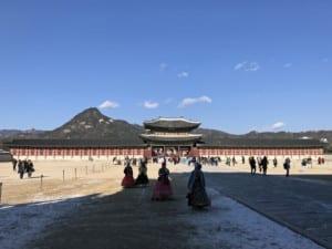 Südkorea | Seoul, Besucher des Gyeongbokgung Palast in traditionellen Kleidern bei blauem Himmel