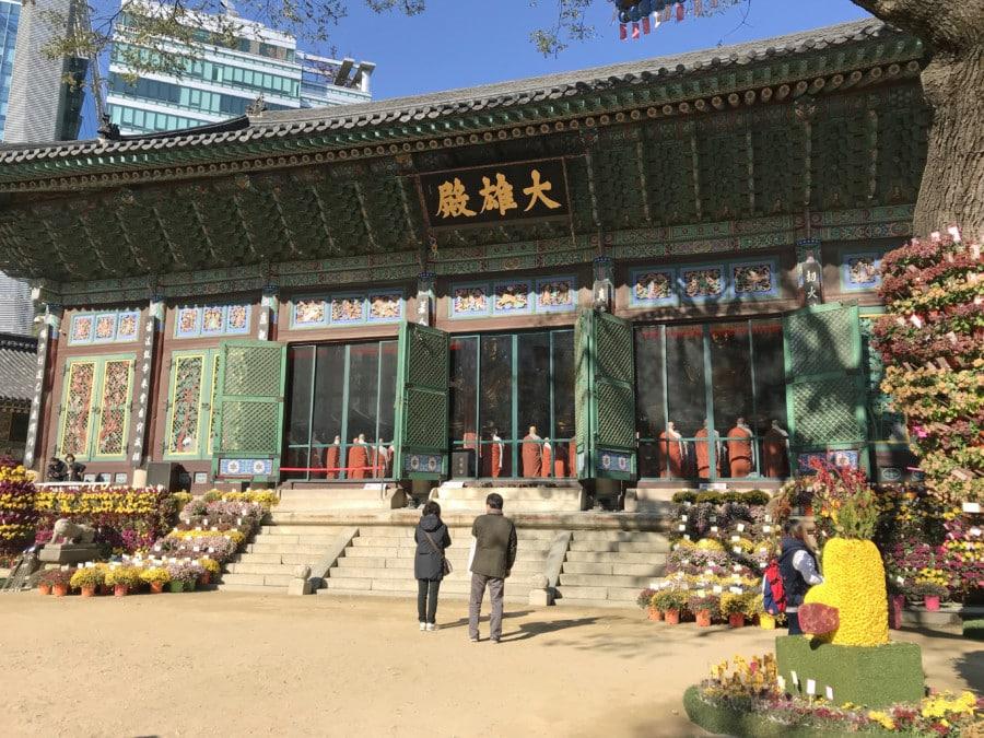 Südkorea | Seoul-Sehenswürdigkeiten & interessante Orte: betende Mönche im Jogyesa Tempel. In orangefarbenen Kutten stehen die Männer amFenster des Tempels, der außen mit Blumen geschmückt ist