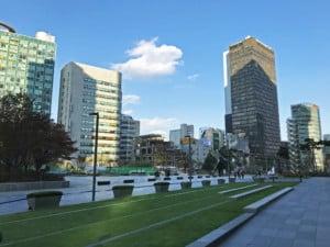 Südkorea | Seoul, Jongno-gu modernes Zentrum. Blick auf Hochhäusern und einen Platz mit Rasen bei blauem Himmel